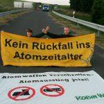 """Zwei Aktivist*innen und zwei Banner (""""Kein Rückfall ins Atomzeitalter"""" und """" Atomwaffen verschrotten - Atomausstieg jetzt! Robin Wood"""") vor Tor 1 des Fliegerhorstes in Büchel"""